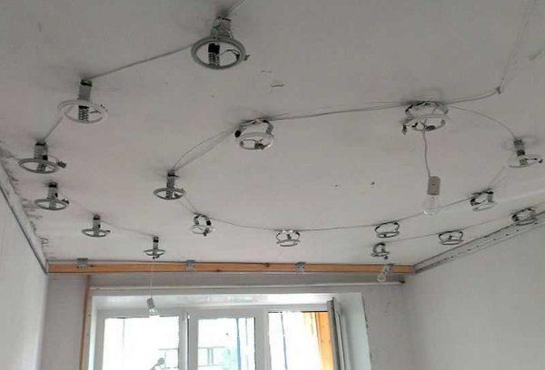 Установленные под натяжным потолком стойки для точечных светильников